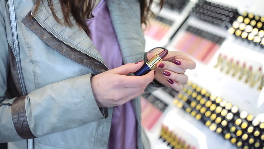 Young woman chooses lipstick in cosmetics store