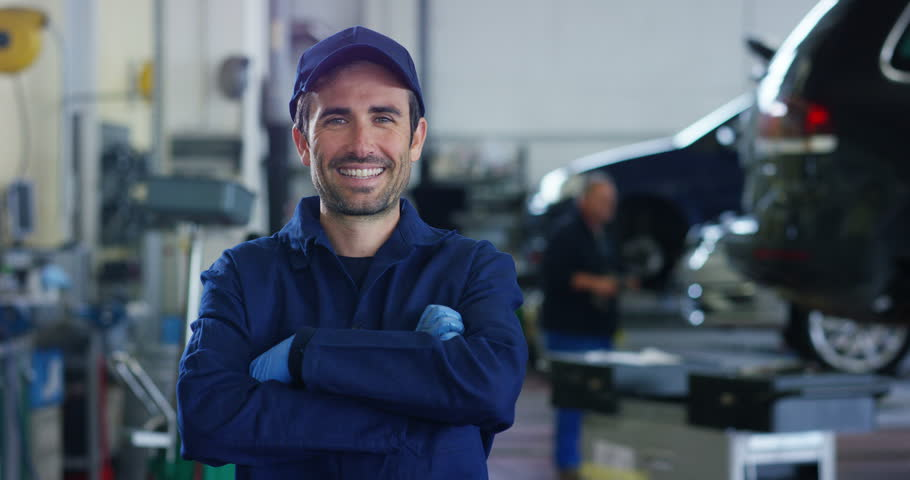 Portrait of a young beautiful car mechanic in a car workshop, in the background of service. Concept: repair of machines, fault diagnosis, repair specialist, technical maintenance and on-board computer