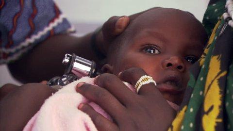 Child getting an ear exam in a Tanzanian clinic