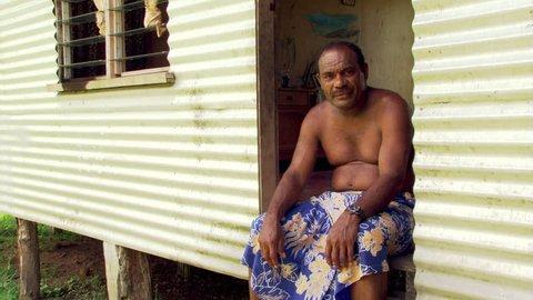 Shirtless Fijian man seated in doorway of house