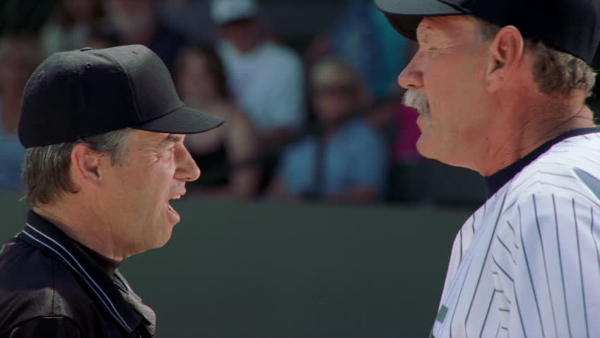 Close-up profiles of a coach and an umpire having an altercation