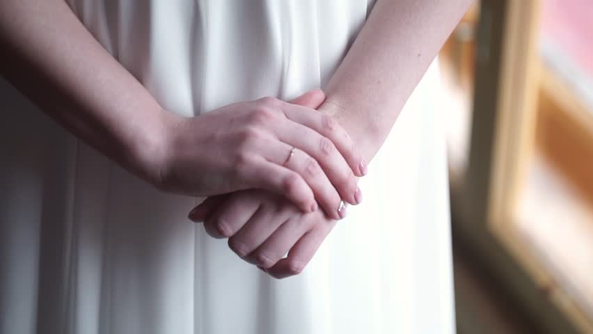 Gold wedding rings and hands of just married couple close up on girl in white dress staying near the window girls hand with wedding ring or engagement junglespirit Choice Image