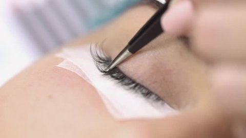 Eyelash extension,makeup artist takes with forceps and stick artificial lashes on the woman's eye,extreme close up,studio beauty,professional procedures eyelash extensions,no color grading,indoors.