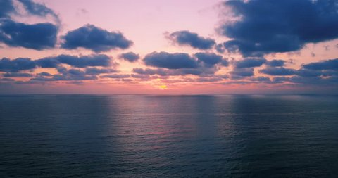 Brightly colored sunset over the calm Mediterranean Sea. Drone Point of View . Night