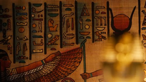Pan shot focusing at first on Egyptian papyrus and then on a pharaoh mask artifact.