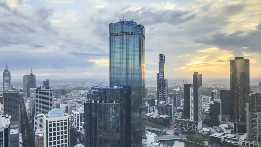 Rolling Clouds, sun rays burst through the clouds during sunrise summer. 4k time lapse of Melbourne city skyline, view from high level building. Zoom out