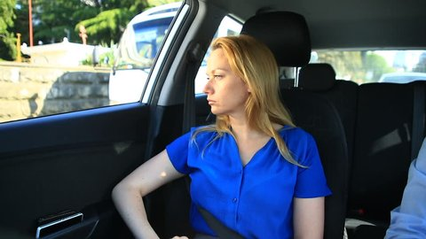 Girl rides in the car next to the driver and sad looks out the window