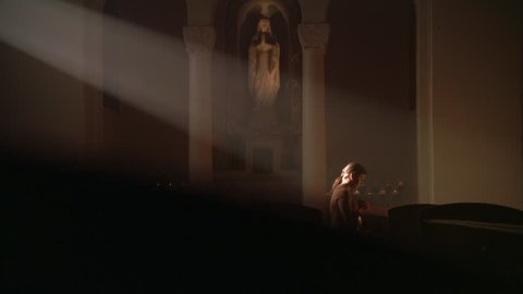 Woman kneeling in ray of sunlight in Catholic church