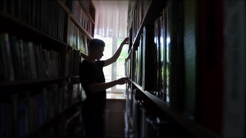 Guy student chose the right book for study or reading, filmed silhouette in the daytime, among the shelves among the books and camera movement | Shutterstock HD Video #26587232
