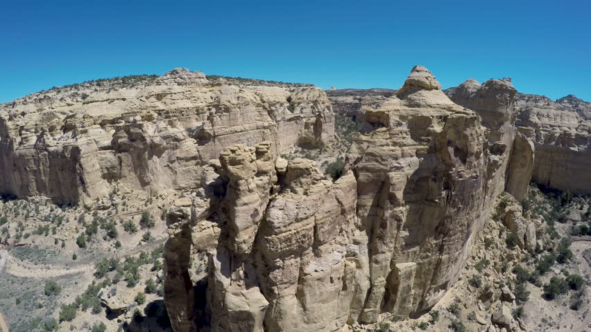 Aerial-descending view of the rugged sandstone monolith of Eagle Canyon Arch in the San Rafael Swell desert on a sunny day with a clear blue sky