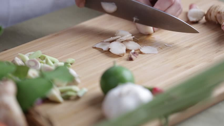 Female hand slice galanga in pieces on bamboo wooden plate with other Thai herbs beside for Tom Yum recipe.