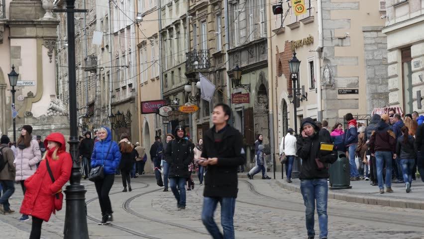 Lviv, Ukraine - April 08, 2017: Citizens and tourists walk and rest on Market Square in Lviv.