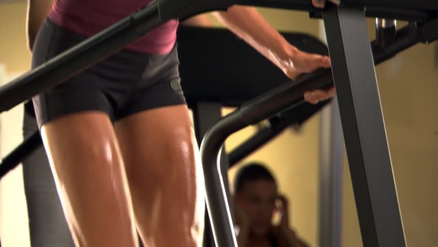 Close-up feet of woman on stair-climbing machine in a fitness club