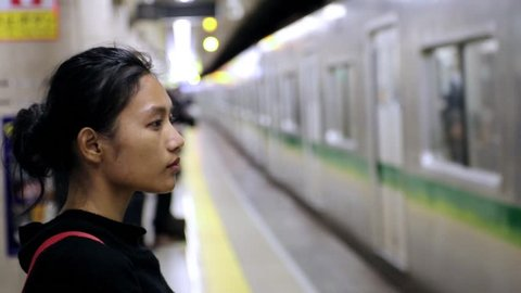 The train arrives at the metro station. People are waiting for the train. Portrait of a woman in a subway station when a train arrives.