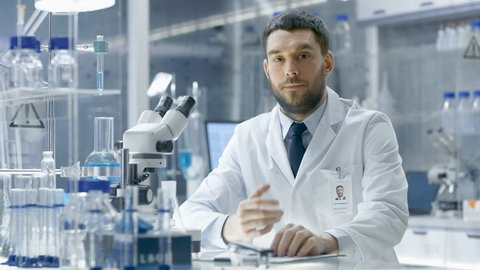 Young Male Research Scientist Talks Into Camera. He's Sitting in a High-End Modern Laboratory with Beakers, Glassware, Microscope and Working Monitors Surround Him. Shot on RED EPIC-W 8K Helium Camera