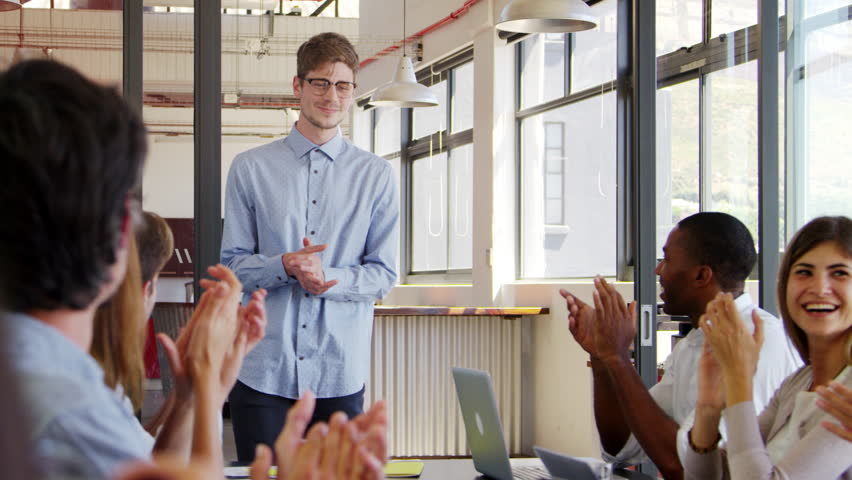 Young man stands clapping with seated colleagues at meeting | Shutterstock HD Video #26647312