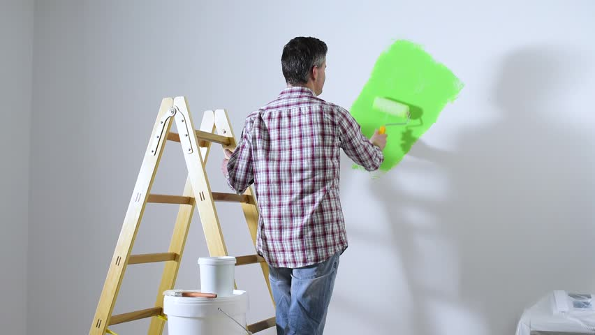 Man Painting Interior Walls At Home Using A Paint Roller He Turns And Smiles Camera Renovation Redecoration Concept