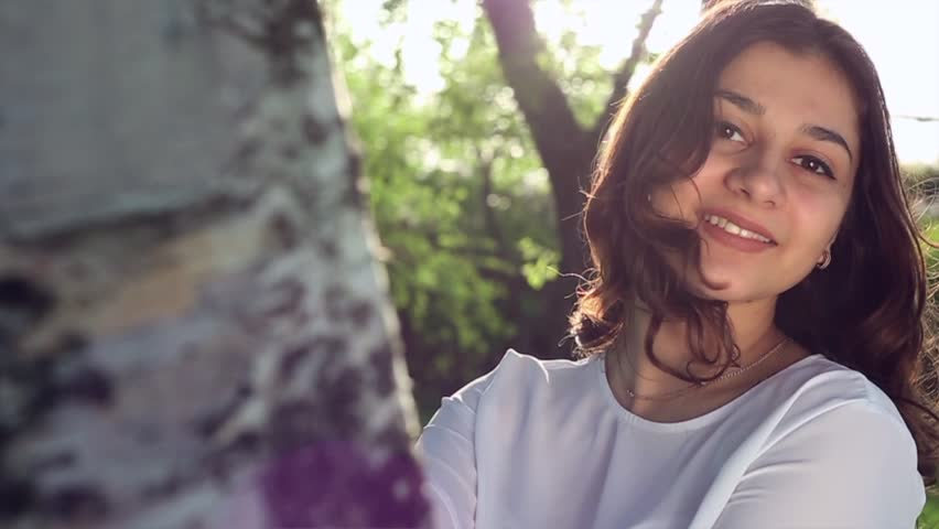 The girl is looking at the camera. Beautiful woman in nature smiling. Sexy brunette with beautiful eyes.