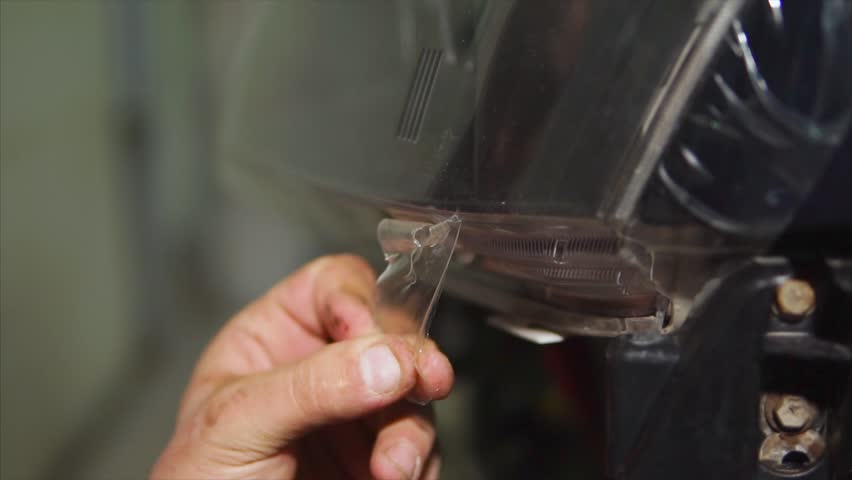 Close up shot of the car expert hands who tear off the vinyl film on the headlights of blue expensive car. This film protects the vehicle from the small chips and scratches.