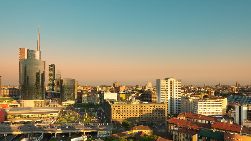 Timelapse of milan city skyline at sunset from day to night aerial view