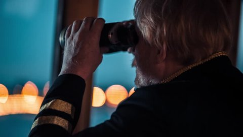 Sailor man looking through the binoculars against Saint-Petersburg on the background