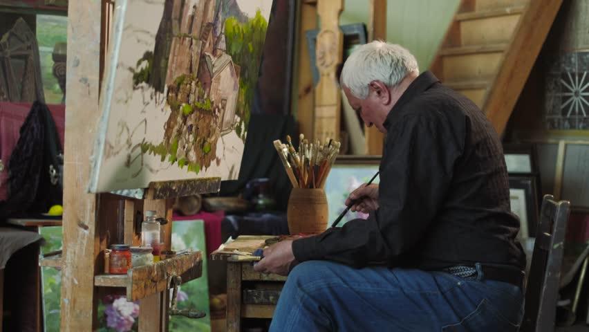 An elderly artist writes a picture in his studio | Shutterstock HD Video #26684362