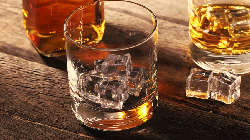 Pouring whiskey into a glass with ice cubes on old wooden table | Shutterstock HD Video #26685052