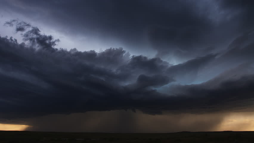 Thunderclouds with pouring rain and multiple lightning flashes looming over dark prairie