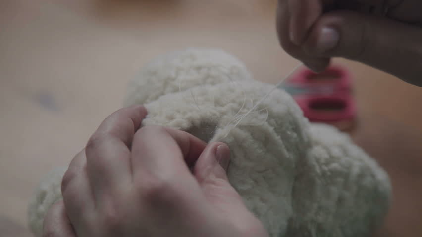 Repair of plush toys: female hands sew a teddy bear. Creating soft handmade toys. Needle and thread in hand of a woman - she sews the details of a soft toy. The process of sewing the details of a toy | Shutterstock HD Video #26708362