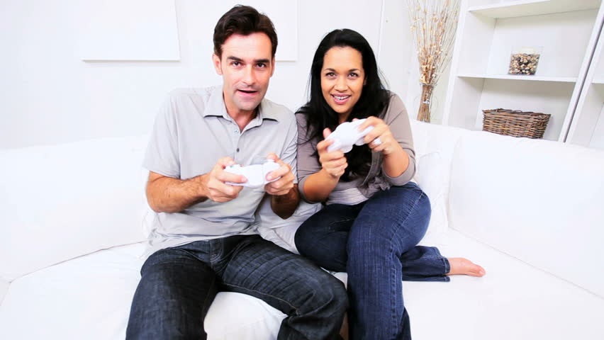 Attractive heterosexual ethnic couple having fun modern electronic games console