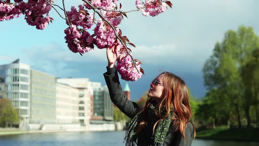 Young girl smelling a sakura. Looping movie. Cinemagraph