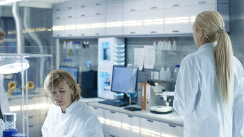 Follow up Shot of Young Laboratory Assistant Walking to Her Workplace.Male and Female Scientists of Different Age Working in this State of the Art Laboratory.Shot on RED EPIC-W 8K Helium Cinema Camera