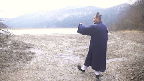 Asian Martial Arts Baguazhang Stances Training in Frozen Landscape 4K. Wide jib shot of man in focus wearing traditional blue kimono clothes concentrated on attacks and defence in stances.