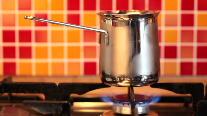 Brewing a turkish style coffee in stainless steel cezve on a gas stove