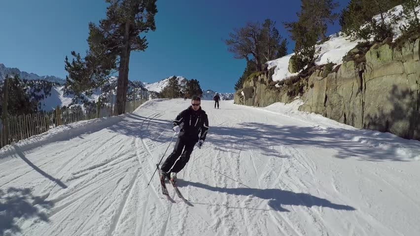 On a Sunny winter's day, a skier in a black suit rolls a carving ski on the ski slope in the mountains, it is removed on the action camera, slow mo.