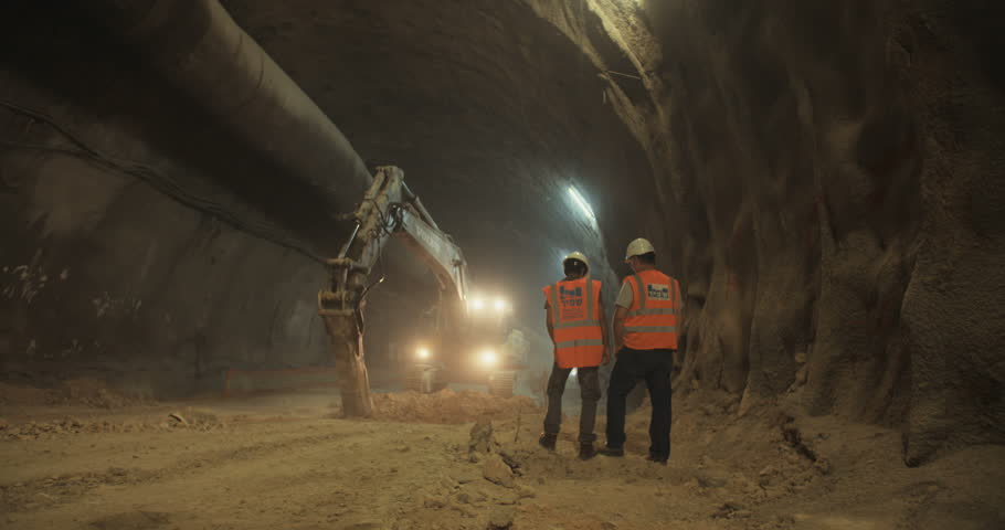 Construction workers supervising heavy machinery during tunnel construction work