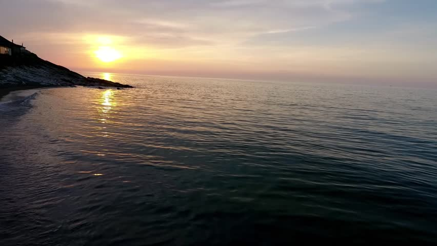 Shot of a beautiful summer sunset at the beach. Waves gently wash up onto the beach, then recede as the sunset.