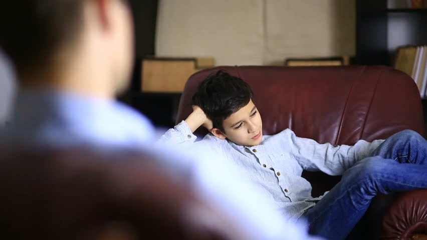 The male therapist conducts a psychological consultation with a teenager. Boy teenager at the reception of a psychologist