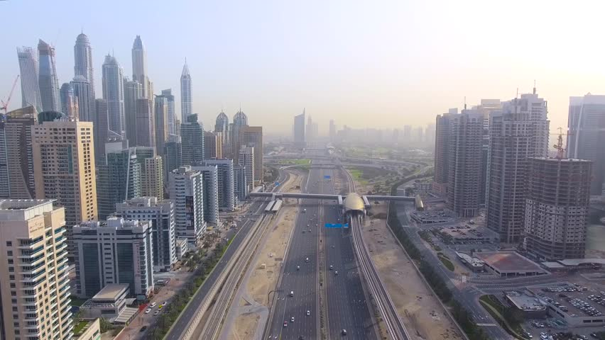Copter fly beside with roads and skyscrapers of Dubai
