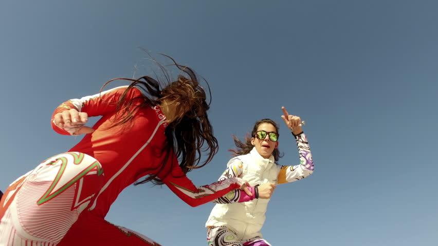 BANSKO, BULGARIA - circa FEB, 2017: Two happy ski girls dancing at outdoors party stage in Bansko ski resort, Bulgaria