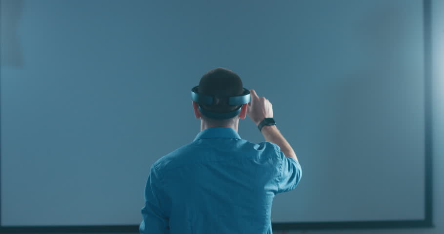 Back view of young adult Caucasian male using holographic augmented reality glasses. 4K UHD RAW edited footage