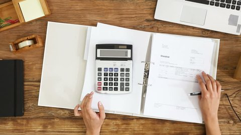 Elevated View Of A Businesswoman Calculating Invoice Using Calculator On Office Desk