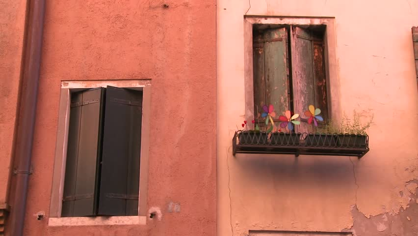 VENICE, ITALY-CIRCA 2011-Pinwheels spin in a planter outside an old window in Venice, Italy.