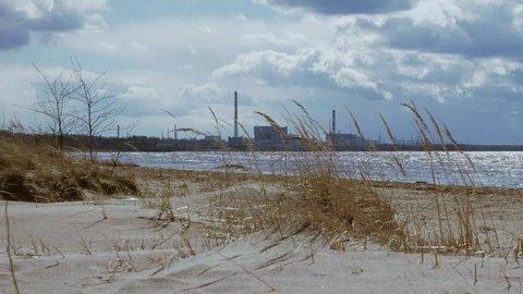 Lonely cold sunny seascape of Baltic sea in spring. View of Leningrad NPP. Leningradskaya oblast.