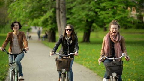Three Active Young Women are Riding Together in the City Park. Smiling Brunettes with Bicycles Outdoors.