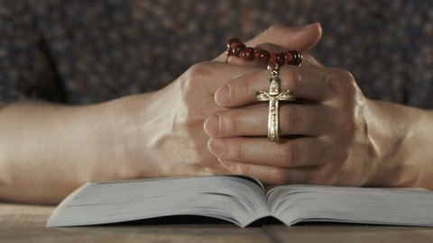 Woman praying with her bible on wooden table