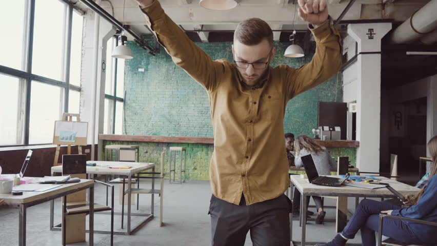 Handsome young businessman doing victory dance about successful achievement. Happy male at modern trendy office. | Shutterstock HD Video #26820115