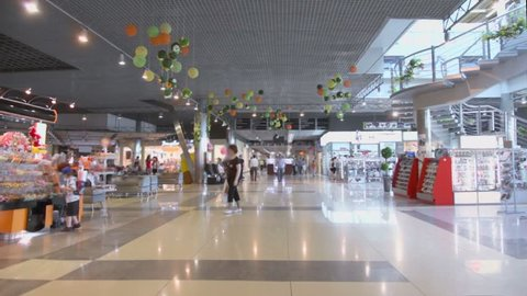 Many customers walk around multilevel shopping center with staircase