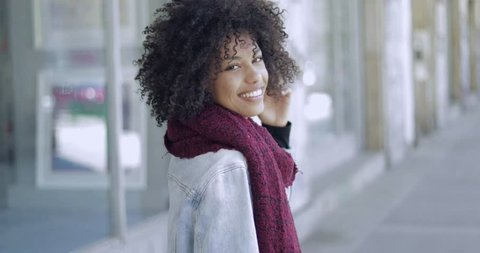 Charming African woman in scarf and jacket with short curls looking at camera and smiling on background of street.
