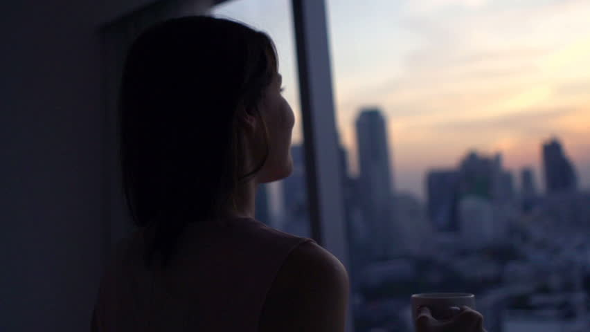 Happy woman drinking coffee and admire view during sunset by window